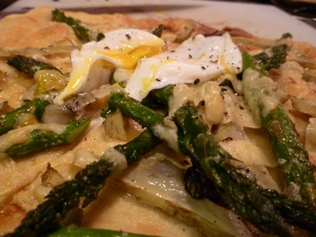 Asparagus, artichoke pizza topped with a poached egg