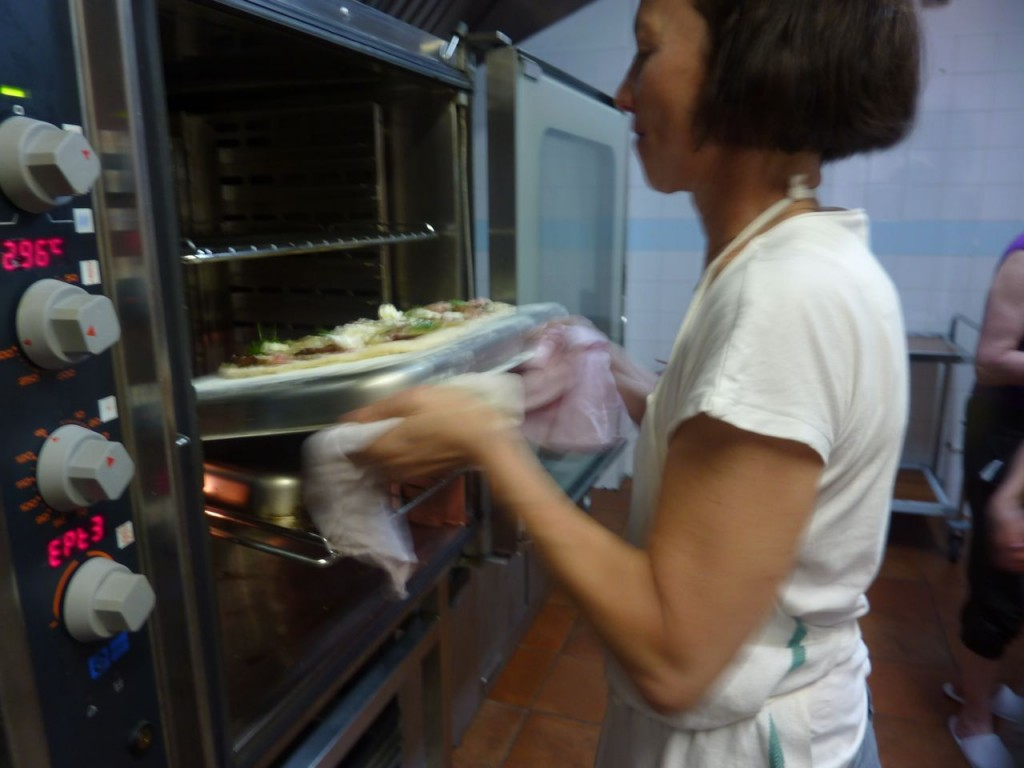 Susan Regis putting pizza in oven - luxury bike tours italy
